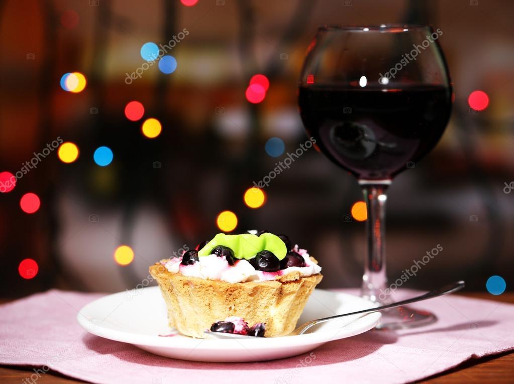 Blackberry sabroso pastel y vaso de vino tinto, sobre fondo oscuro