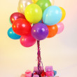 Many bright balloons and many gifts on light background — Stock Photo