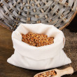 Grains in sack on wooden background — Stock Photo #24940183
