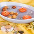 Stock Photo: Beautiful candles swim in beautiful plate on yellow fabric close-up
