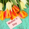 Stock Photo: Beautiful white and orange tulips on color wooden background