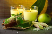 Hand made soap and candles on bamboo mat background — Stock Photo