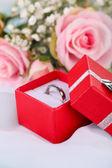Rosor och en ring på en vit duk — Stockfoto