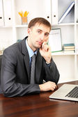 Young businessman in office at his workplace — Stock Photo