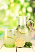 Citrus lemonade in pitcher and glass on wooden table on natural background — Stockfoto