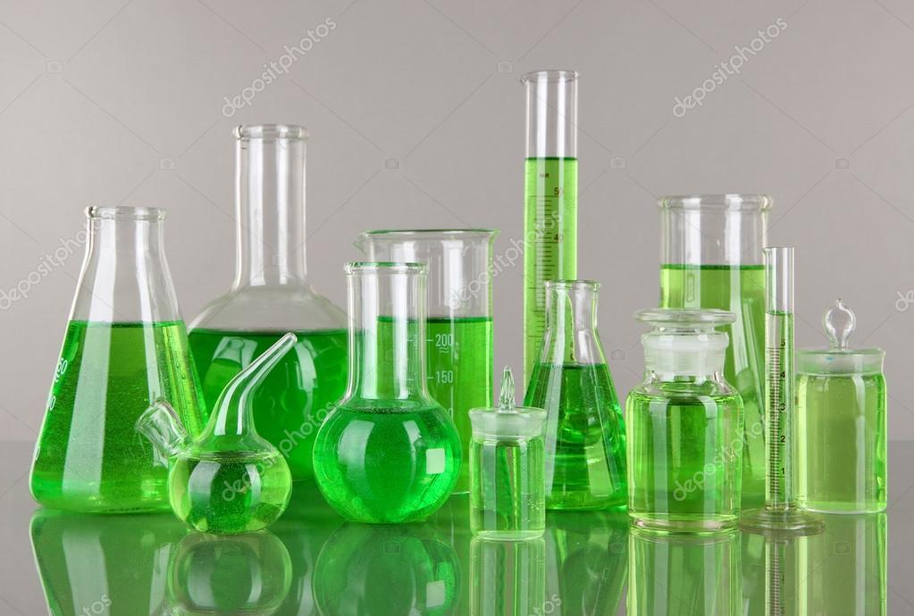 试管与灰色的背景上的绿色液体