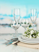 Serving dishes and snowdrops on blue natural background — Stock Photo