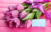Beautiful bouquet of purple tulips on pink wooden background — Zdjęcie stockowe