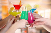 Cocktails in hands in cafe — Stock Photo