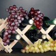Stock Photo: Bottles of wine placed on wooden stand on grey background