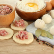 Raw dumplings, ingredients and dough, on wooden table — Stock Photo #25030537