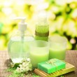 Cosmetics bottles and natural handmade soap on green background — Stock Photo