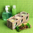 Candles in wooden candlestick, cosmetics bottles and soap, on green bamboo mat — Stock Photo