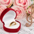 Treble clef, roses and box holding wedding ring on musical background — Stock Photo #25036741