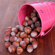 Overturned bucket with hazelnuts on wooden background — Stock Photo