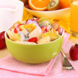 Useful fruit salad of fresh fruits and berries in bowl on napkin on wooden table close-up — Stock Photo #25038165