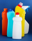 Different kinds of bath and toilet cleaners and colorful sponges, on color background — Stock Photo