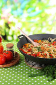 Noodles with vegetables on wok on nature background — Stock Photo