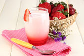 Delicious strawberry yogurt in glass on wooden table close-up — Stock Photo
