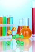 Modello di molecola e provette con liquidi colorati su sfondo blu — Foto Stock