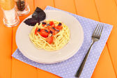 Spaghetti with tomatoes and basil leaves on napkin on wooden background — ストック写真