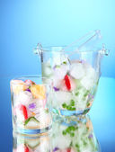 Ice cubes with flowers, fruit pieces and herbs in glass and glass bucket, on blue background — Stock Photo