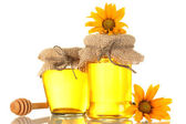 Sweet honey in jars with wooden drizzler and flowers isolated on white — Stock Photo