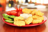 Fried chicken nuggets with vegetables and sauce on table in cafe — Stock Photo