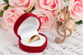 Treble clef, roses and box holding wedding ring on musical background — Stockfoto