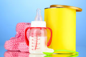 Bottle with milk and food for babies on blue background — Stock Photo