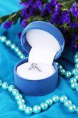 çiçekler ve mavi kumaş üzerine nişan yüzüğü — Stok fotoğraf