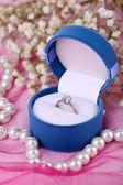 Förlovningsring på rosa tyg — Stockfoto