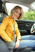 Portrait of young beautiful woman attaching seat belt in the car — Foto Stock