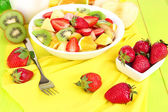 Useful fruit salad of fresh fruits and berries in bowl on tablecloth close-up — Stock Photo
