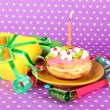 Colorful birthday cake with candle and gifts on pink background — Photo