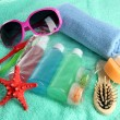 Hotel cosmetics kit on blue towel — Stock Photo #25093433