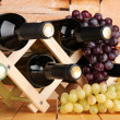 Stock Photo: Bottles of wine placed on wooden stand on stone wall background