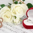Treble clef, roses and box holding wedding ring on musical background — Stock Photo #25093827