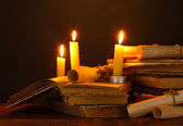 Pile of old books with candle and scroll in dark — Stock Photo