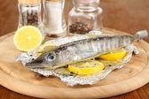 Folyo otlar ve ahşap masa yakın çekim üzerinde kurulu limon ile balık — Stok fotoğraf