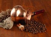 Cezve kahve çekirdekleri kahverengi ahşap zemin ile — Stok fotoğraf