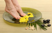 Female feet in spa bowl with water, on bamboo mat — Stock Photo