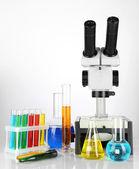 Zkumavky s barevnými tekutinami a mikroskop izolovaných na bílém — Stock fotografie