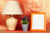 Colorful photo frame, lamp and flowers on wooden table on red background — Stock Photo