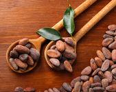 Kakaobohnen mit blättern in löffel auf hölzernen hintergrund — Stockfoto