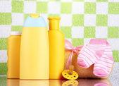 Cosmétiques bébé et serviette dans la salle de bain vert carreaux fond mur — Photo