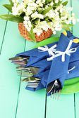 Fork and knife wrapped in blue paper napkin, on color wooden background — Stock Photo