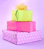 Bright gifts with bows on purple background — Stock Photo