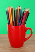 Colorful pencils in cup on table on green background — Stok fotoğraf