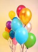 Many bright balloons on orange background — Stock Photo